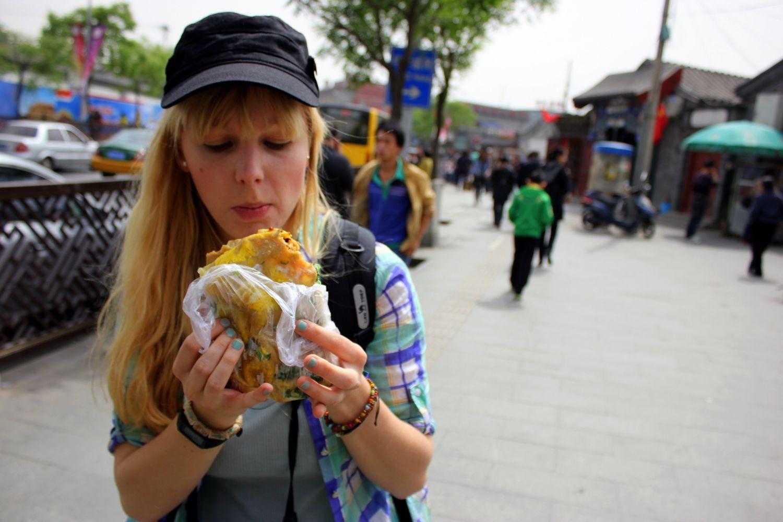 Agness eating Beijing street desserts