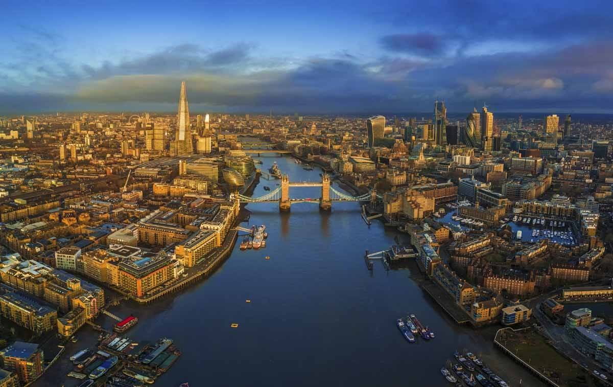London, England - Panoramic aerial skyline view of London including iconic Tower Bridge with red double-decker bus, Tower of London, skyscrapers of Bank District and other famous skyscrapers at golden hour early in the morning with colorful sky and clouds
